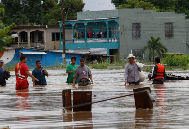 Men wade through a street flooded after the passing of Hurricane Iota in La Lima, Honduras, Wednesday, Nov. 18, 2020.