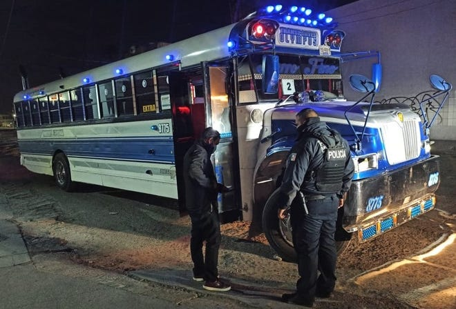 A police officer inspects a bus while enforcing a nightly curfew and transportation restrictions intended to fight the spread of COVID-19 in Juárez, Mexico, in November 2020.