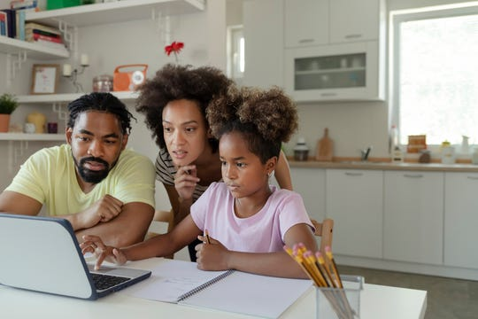 Parents help their child with online learning.