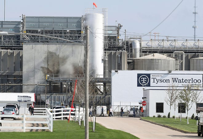 Tyson's Fresh Meat workers file in for a tour of safety measures put into place after the plant in Waterloo, Iowa, had to shut down due to a COVID-19 outbreak.  Lawyers for the estates of dead workers allege that the top official at Tyson Foods' largest pork plant created a pool for managers to bet on how many workers would get infected during a coronavirus outbreak.