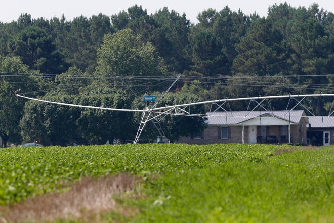 An irrigation system is seen in front of a home across the road from a farm that has hogs owned by Smithfield Foods in Farmville, N.C. A federal appeals court on Thursday, Nov. 19, 2020 upheld a 2018 jury verdict that led to awarding monetary damages to neighbors of a North Carolina industrial hog operation for smells and noise they said made living nearby unbearable.