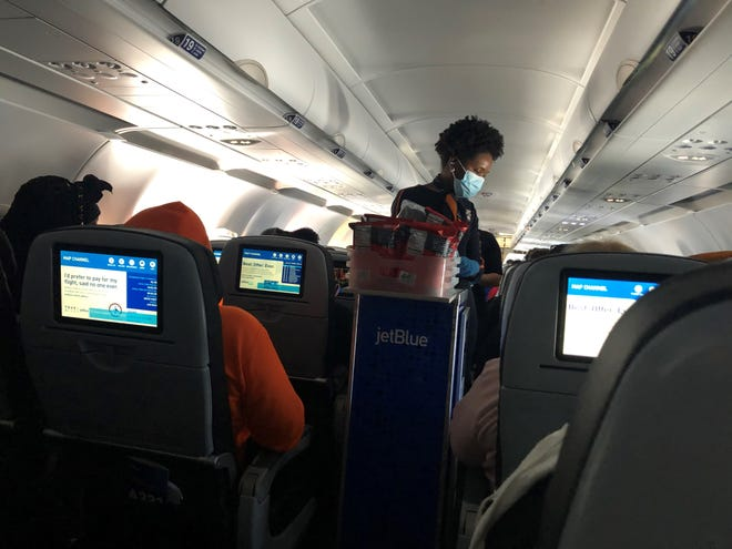 A JetBlue Airways flight attendant serves passengers snacks on a flight from New York to Cancun, Mexico. JetBlue has among the most generous free snack offerings during the pandemic.