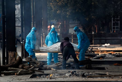 Health workers in personal protective equipment carry the body of a COVID-19 victim for cremation in New Delhi, India, Thursday, Nov. 19, 2020. India's confirmed coronavirus caseload is expected to surpass 9 million on Friday as authorities in New Delhi battle to slow down the surge of infections in the city by increasing testing.