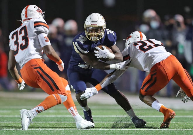Hoban running back Lamar Sperling, center, sheds Massillon defensive back Andrew Wilson-Lamp as he cuts across the field for yards during the first half of the Division II state championship game, Friday, Nov. 20, 2020, in Massillon, Ohio. [Jeff Lange/Beacon Journal]