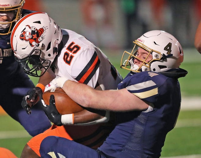 Archbishop Hoban linebacker Luke Bauer, right, brings down Massillon running back Willtrell Hartson during the first half of the Division II state championship game. Bauer signed his national letter of intent with the University of Akron on Wednesday. [Jeff Lange/Beacon Journal]