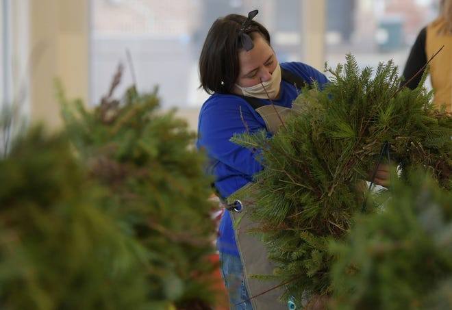 Janine Roberson makes Christmas wreaths in her stand at Ames Main Street Indoor Farmer Market in downtown Ames Saturday, Nov. 21, 2020.