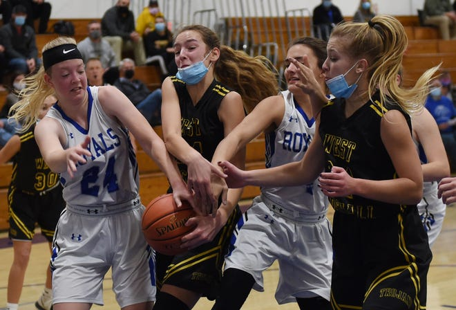 Colo-Nesco's Emma Wilson (left) and Callie Kohlwes battle West Marshall's Katy Reyerson (center) and Delaney Nichols battle for a loose ball during the first quarter of the Royals' 42-30 loss to the Trojans to open the girls' basketball season Friday at Colo.