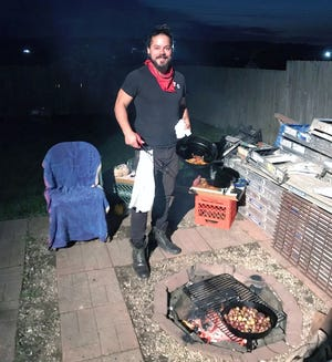 Josh Knopp of New Sewickley Township cooks traditional hibachi in a cast iron pan over an open flame. He combined his love of the outdoors and cooking into a business that has taken him all over western Pennsylvania as word has spread about Knopp's wood-fire meals.