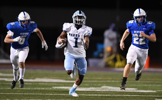 Central Valley's Myles Walker splits Bedford defenders Steven Ressler, left, and Ethan Weber, right, on his way to a 82-yard touchdown run during a PIAA 3A semifinal Friday at Mansion Park in Altoona.