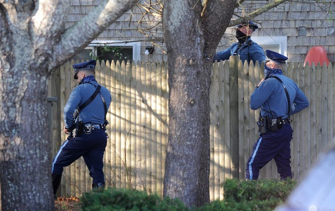 Police form a perimeter around the Hastings Meadow condominium complex off West Main Street in Hyannis on Saturday morning during an investigation into the shooting of a state trooper Friday night.