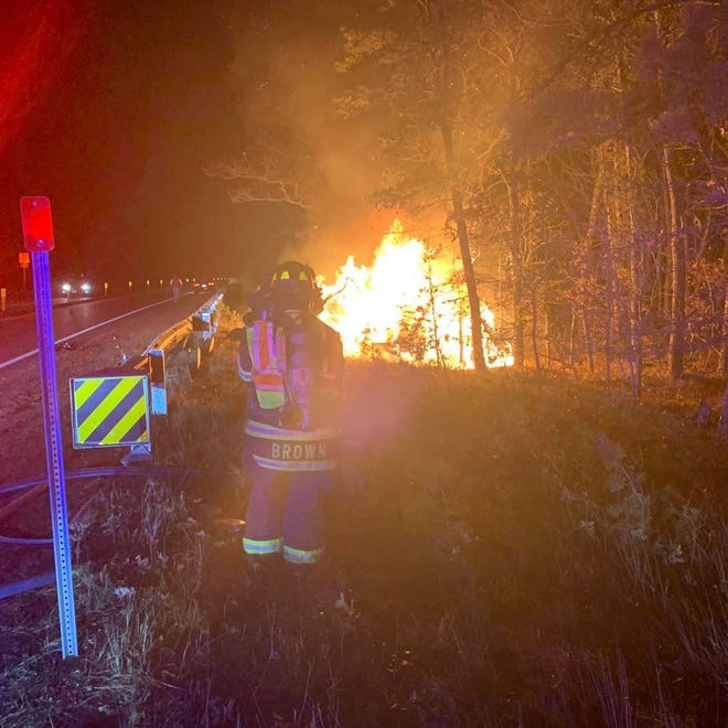Firefighters work at the scene where a car rolled over and caught fire near the Route 6 rest area in Harwich on Friday night. An off-duty firefighter and a bystander rescued the driver from the vehicle.