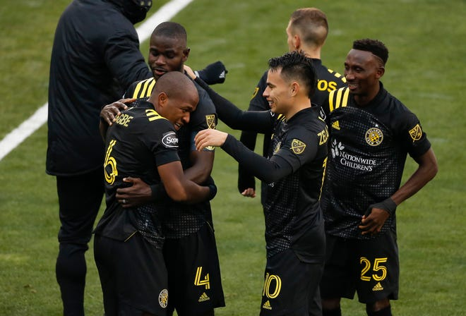 Columbus Crew SC defender Jonathan Mensah (4), midfielder Lucas Zelarayan (10) and defender Harrison Afful (25) congratulate midfielder Darlington Nagbe (6) on scoring a goal during the second half of the MLS Cup playoff match against the New York Red Bulls at Mapfre Stadium in Columbus on Saturday, Nov. 21, 2020. The Crew won 3-2.