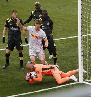 Columbus Crew SC goalkeeper Eloy Room (1) makes a save in front of New York Red Bulls forward Tom Barlow (74) during the first half of the MLS Cup playoff match at Mapfre Stadium in Columbus on Saturday, Nov. 21, 2020.