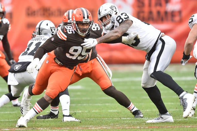Cleveland Browns defensive end Myles Garrett (95) runs around Las Vegas Raiders tight end Darren Waller (83) on Nov. 1 in Cleveland. Garrett was activated from the COVID-19 list after missing the past two games. (AP Photo/David Richard)