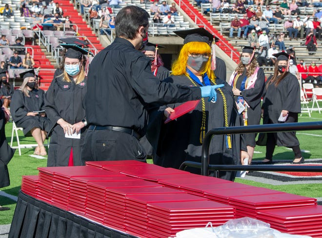 Officials observe COVID protocols in handing out diplomas during Nicholls State University's fall commencement ceremonies at John L. Guidry stadium on Saturday.