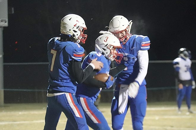 Tom Martushev (3) is congratulated by Jonas Spry (7) and Kobe Hamre (1) after his touchdown in the second quarter of Win-E-Mac's 50-0 win over South Ridge on Friday night in Erskine.