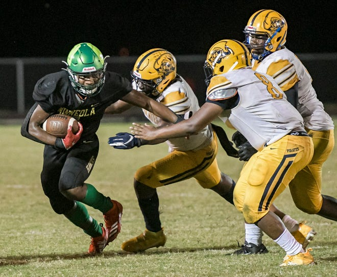 Lake Minneola's Duke Walker (5) runs away from a pack of defenders during Friday's Class 6A-Region 2 quarterfinal game against Gulfport Boca Ciega at Lake Minneola. [PAUL RYAN / CORRESPONDENT]