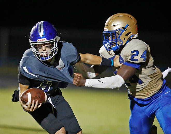 Isaiah Gordon (24) wraps up Matanzas quarterback Ethan Dattilio for a sack in Friday's Region 1-6A quarterfinal.