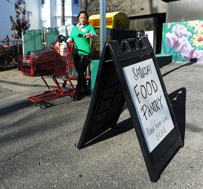 Worker Tanya Miranda brings a shopping cart of food to a client at the Charity Guild Food Pantry and Thrift Store, 501 Main St. in Brockton, on Saturday, Nov. 21, 2020.