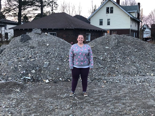 Taylor Richardson stands about where her living room once stood at 11 Preston Avenue, before the fire consumed much of the street a year ago.