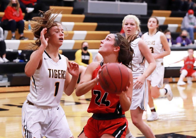 Winfield-Mt. Union's Kyndal Townsley (24) looks to the basket while guarded by New London's Natalie Burden.