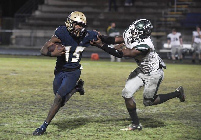 Sandalwood quarterback Chris Calhoun (15) runs away from Flagler Palm Coast linebacker Malakai Grant (30) during a November football playoff.