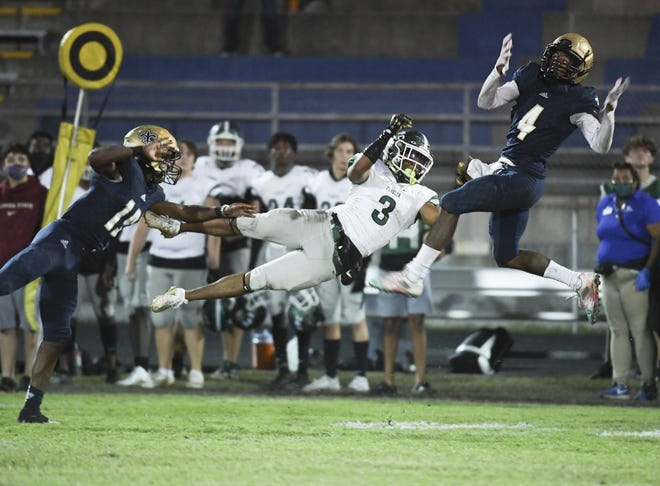 Sandalwood defensive back Jadon Canady (4), right, and Flagler Palm Coast receiver Ty-shawn Blount leap for a pass downfield during the Region 1-8A quarterfinal.