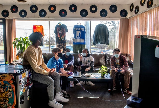 Logan Milligan, far right, owner of Hindsight, a vintage apparel and skateboard shop at 325 E. Lake Ave. in Peoria Heights, plays video games with a group of Dunlap High School kids after school. Shown from left are Isaiah Curry, Sammey Mustafa, Charles Baker and Kejuan Irby.