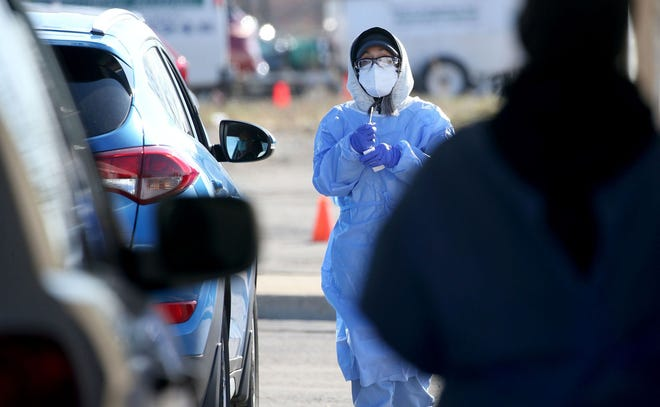 Phlebotomist Tina Novick returns a sample after taking a COVID-19 test at the Illinois Department of Public Health drive-thru site in Aurora on Nov. 12, 2020.
