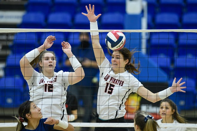 Lubbock-Cooper's Nicole Campbell (12) and Kaitlyn Mayo (15) block a ball against Plainview during a Class 5A bi-district match Nov. 21 at Lubbock Christian University's Rip Griffin Center.