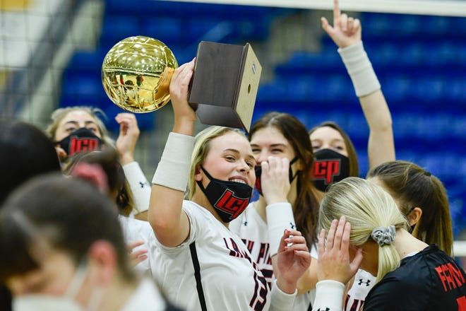 Tatum Farmer (13) holds the Class 5A bidistrict trophy after Lubbock-Cooper earned a 25-11, 25-19, 25-12 win over Plainview on Saturday at Lubbock Christian University's Rip Griffin Center.