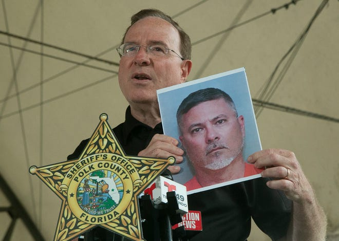 Polk County Sheriff Grady Judd holds a jail booking photo of 46-year-old Shawn Fitzgerald during a news conference to announce Fitzgerald's arrest on 408 counts of possession of child pornography at the Lakes Church in Lakeland on Saturday afternoon. Fitzgerald is a Lakeland High teacher and coach.