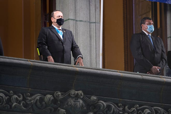 Guatemalan President Alejandro Giammattei, left, and Vice President Guillermo Castillo, both wearing masks as a precaution against the spread of the new coronavirus, take part of the independence day celebrations in Guatemala City, in September.