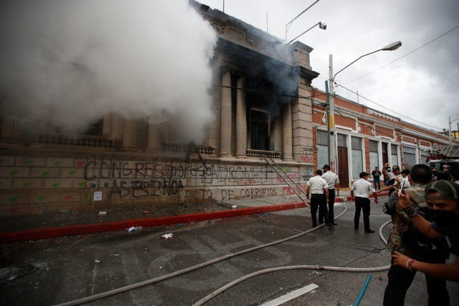 Clouds of smoke shoot out from the Congress building after protesters set it on fire in Guatemala City on Saturday. Hundreds of demonstators were protesting in various parts of the country Saturday against Guatemalan President Alejandro Giammattei and members of Congress for the approval of the 2021 budget that reduced funds for education, health and the fight for human rights.