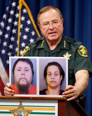 Sheriff Grady Judd speaks as he holds pictures of Kris Peters and Melissa Peters during a press conference on a child abuse case at the Polk County Sheriff's Office in Winter Haven on Nov. 21, 2016.