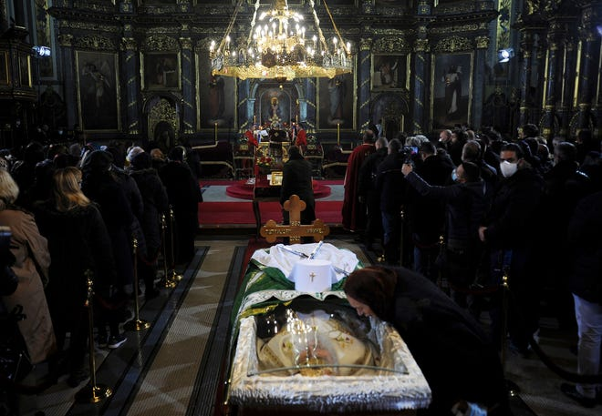 A woman kisses a protective screen over the coffin of Patriarch Irinej as he lies in repose at the Congregational church in Belgrade, Serbia, on Saturday. Mourners flocked to pay respects following the death of the Serbian Orthodox Church Patriarch Irinej, many ignoring preventive measures against the new coronavirus even though the head of the church died after contracting the virus himself.
