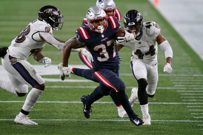 Patriots running back Damien Harris (center) runs past Ravens linebacker Patrick Queen (left) and cornerback Marlon Humphrey in the first half of New England's 23-17 win on Sunday, Nov. 15, 2020. [AP File Photo/Charles Krupa]