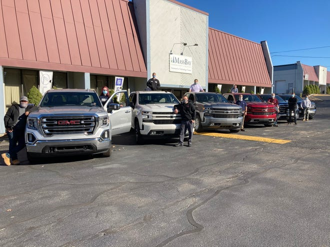 MassBay Community College automotive students and instructors pose with all six donated trucks.