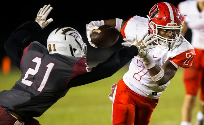 Dunnellon's Demetrius McCants tries to elude North Marion's Chris Foster. The Dunnellon Tigers defeated the North Marion Colts, 13-7, Friday night.