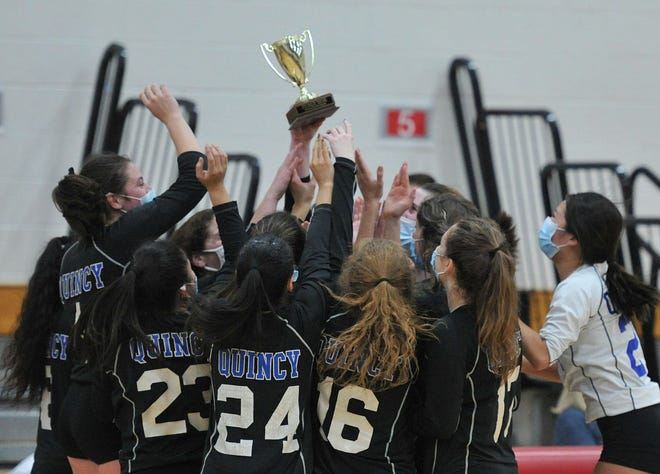 The Quincy Presidents hold high the Patriot League girls volleyball championship trophy after defeating Duxbury at Silver Lake Regional High School, Friday, Nov. 20, 2020.