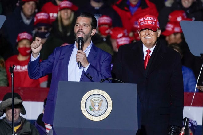President Donald Trump, right, watches as Donald Trump Jr. speaks at a campaign event in Kenosha, Wisconsin, on Nov. 2. A spokesman says Donald Trump Jr. has been infected with the coronavirus.