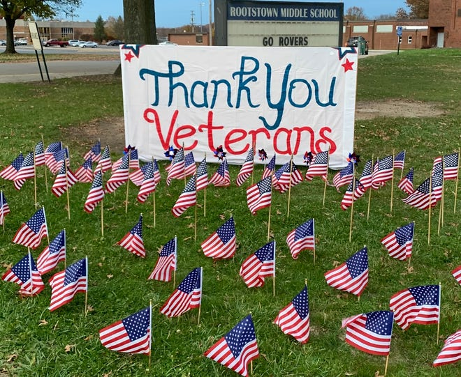 Flags in the front yard of Rootstown Middle School welcome veterans as they enter the bus lane for the drive-thru parade.