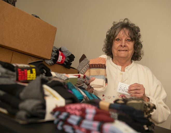 Linda Carlisle with piles of socks for the Sock It To Me non-profit organization that primarily donates socks, but also has been donated bottles of water and toys.