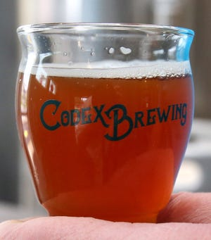 Jason Gasper-Hulvat, owner and brewer at Codex Brewing, holds a sample at his business in Jackson Township on Saturday, Nov. 21, 2020.