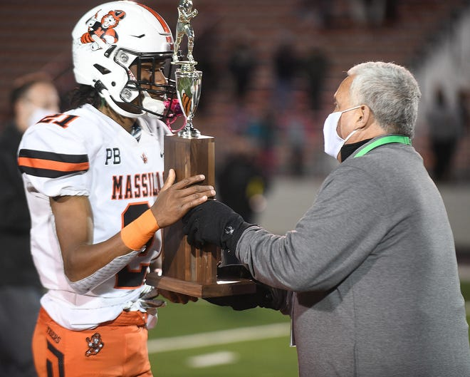 Doug Ute, Executive Director of the Ohio High School Athletic Society presents Massillon team captain Andrew Wilson- Lamp with the Div. II state runner -up trophy.