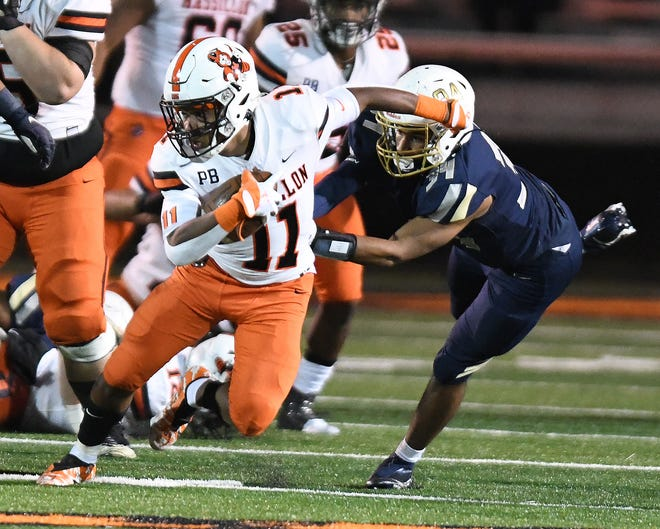 Massillon receiver Martavien Johnson tries to elude the tackle of  of Hoban defender Markim McKinnie in the first half.