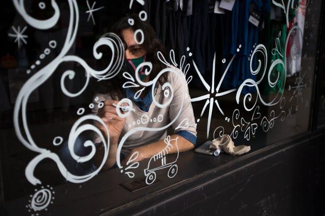Rockford mural artist Jenny Mathews paints on the State Street windows at Rockford Art Deli on Friday, Nov. 20, 2020, in Rockford.