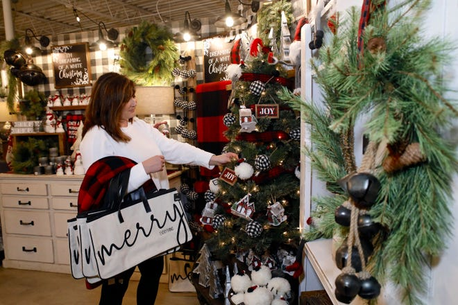 Urban Farmgirl owner Mary Gulbrantson works on holiday merchandise displays Friday in the downtown warehouse showroom at 716 N. Madison St., Rockford.