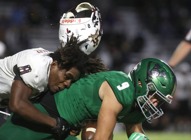 Riverdale's Brandon Walters (8) loses his helmet as he brings down Venice High's Weston Wolff (9) during Friday night's Class 7A high school football game at Powell-Davis Stadium in Venice.