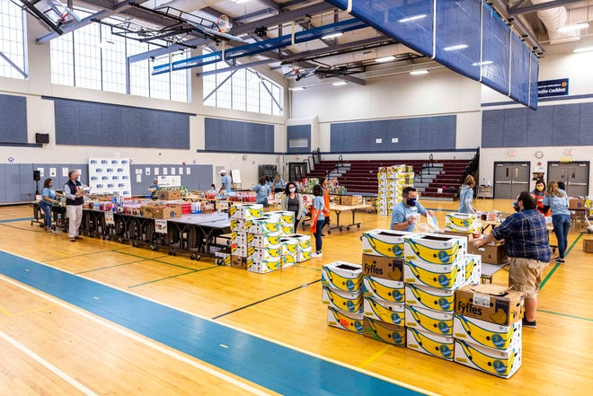 The Greater New Bedford United Way's Hunger Heroes Project, works on making up boxed goods for Thanksgiving meals at Keith Middle School.  RYAN FEENEY/STANDARD-TIMES]